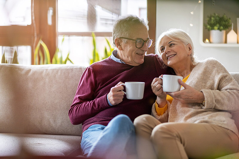 Elderly couple on couch with coffee
